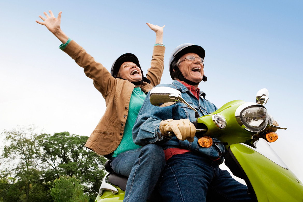 Happy senior couple riding a scooter