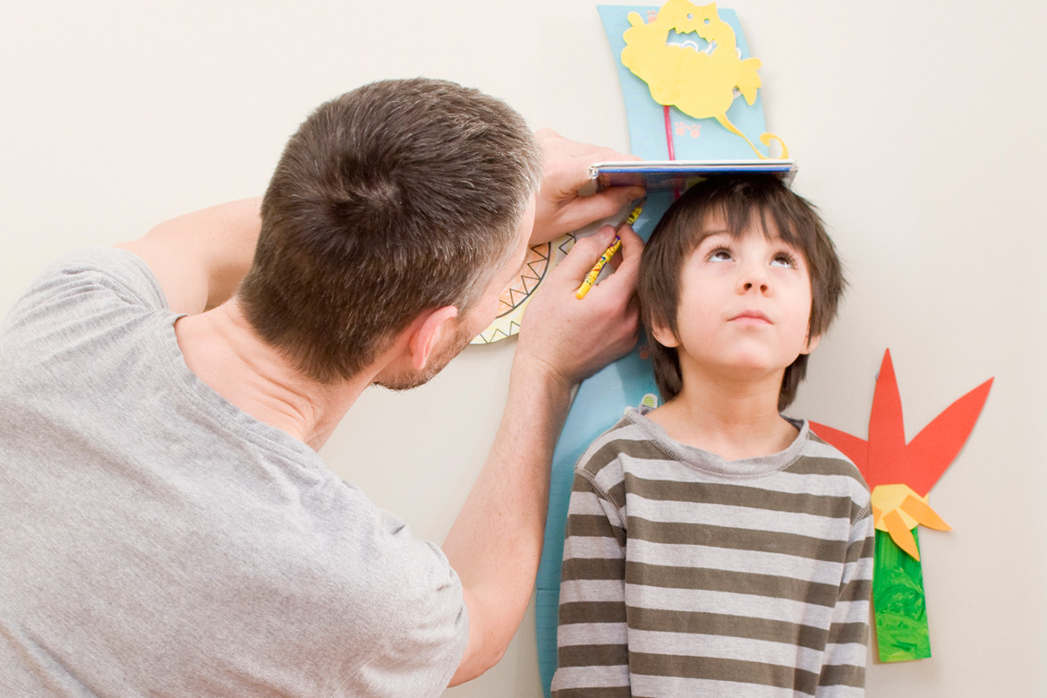 Father measuring son's height on growth chart