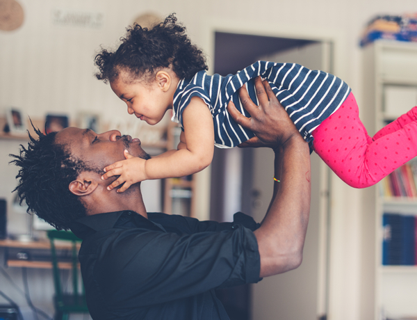 Father holding young daughter up in the air